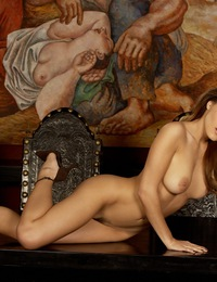 Andie Valentino passionately arching her back making her naked breasts and long lithe body more prominent against a beautiful mural backdrop.